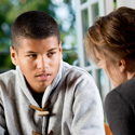Serious Young Man Talking To Counsellor or Teacher